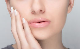 Natural Makeup and French Manicure. Sensual Lips. Portrait macro of young woman with piercing, natural makeup and french manicure Royalty Free Stock Photo