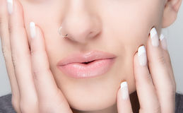 Natural Makeup and French Manicure. Sensual Lips. Portrait macro of young woman with piercing, natural makeup and french manicure Royalty Free Stock Images