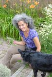 Natural mature woman working in garden with Border collie Royalty Free Stock Photo
