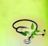 Natural medicine. Background concept with stethoscope and green plant like a sign of health Royalty Free Stock Photo