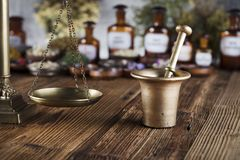 Alternative medicine.  Place for logo and text. Natural medicine background. Brass mortar, bottles and scale. Rustic table. Assorted dry herbs in bowls. Bokeh Royalty Free Stock Photos