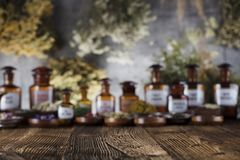Alternative medicine.  Place for logo and text. Natural medicine background. Brass mortar, bottles and scale. Rustic table. Assorted dry herbs in bowls. Bokeh Royalty Free Stock Images