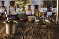 Alternative medicine.  Place for logo and text. Natural medicine background. Brass mortar, bottles and scale. Rustic table. Assorted dry herbs in bowls. Bokeh Stock Image