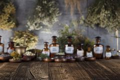 Alternative medicine.  Place for logo and text. Natural medicine background. Brass mortar, bottles and scale. Rustic table. Assorted dry herbs in bowls. Bokeh Stock Images