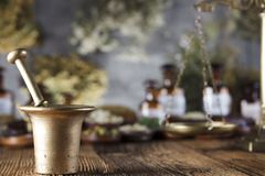 Alternative medicine.  Place for logo and text. Natural medicine background. Brass mortar, bottles and scale. Rustic table. Assorted dry herbs in bowls. Bokeh Stock Photo