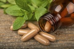 Natural medicine capsules on table royalty free stock photography