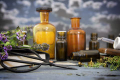 Natural medicine, healing herbs, scissors and apothecary bottles. On blue rustic wood against a dark sky with clouds, selected focus and narrow depth of field stock photos