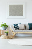Natural minimalist home decor mock-up. Natural minimalist home decor with white wall, mock-up painting, plants, wooden sofa and decorative pillows Stock Photography