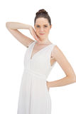 Natural model in white dress posing stroking her face Royalty Free Stock Photo