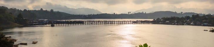 Natural morning sunrise landscape panoramic view of Mon Bridge Thai longest wooden bridge over Songkalia river background in stock photography