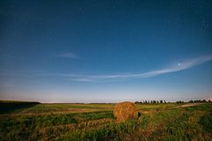 Natural Night Starry Sky Above Field Meadow With Hay Bale After Harvest. Glowing Stars Above Rural Landscape In August