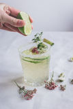 Natural nonalcoholic cocktail with herbs and cut lime on stone desk background. Natural nonalcoholic cocktail with herbs and cut lime for summer party on stone Stock Images