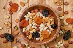 Natural nutritious mix of different nuts with dried apricots and plums in a wooden round plate on the brown wooden table. Mixture stock images