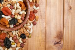 Natural nutritious mix of different nuts with dried apricots and plums in a wooden round plate at the left side. Mixture of walnut royalty free stock photo