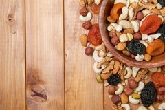 Natural nutritious mix of different nuts with dried apricots and plums in a wooden round plate at the right side. Mixture of walnu royalty free stock photo