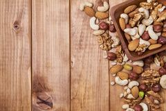 Natural nutritious mix of different nuts in a square wooden plate on brown wooden table at the right side. Mixture of walnuts, huz royalty free stock image