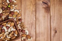 Natural nutritious mix of different nuts in a square wooden plate on brown wooden table at the left side. Mixture of walnuts, huze royalty free stock photography