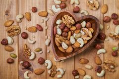 Natural nutritious mix of different nuts in a wooden plate of heart symbol shape on brown wooden table. Mixture of walnuts, huzeln stock image