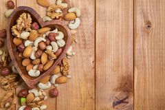 Natural nutritious mix of different nuts in a wooden plate of heart symbol shape on brown wooden table at the left side. Mixture o royalty free stock photo