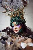 Natural nymph with horns like branches of a tree and butterflies circling around. Fantasy style costume. Young beautiful girl in the image of flora royalty free stock photos