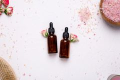 Natural oil bottles with flowers and bath salt on white background royalty free stock photography
