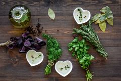 Natural oil and fresh greenery for restaurant cooking on wooden kitchen table background top view. Natural oil and fresh greenery for restaurant cooking with royalty free stock images