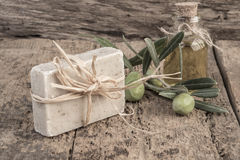 Natural olive oil soap bar and oil bottle on wooden table Stock Images