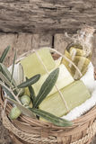 Natural olive oil soap bar and olive oil on wooden table Stock Photos