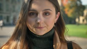 Natural open sight of caucasian female standing straight and looking at camera with beautiful brown eyes, outside, wide. Space on background, casual style stock video footage