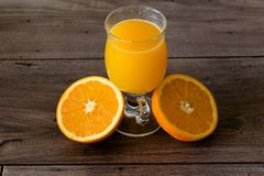 100 percent natural orange juice in a glass. Natural orange juice in a glass on top of a wooden table Stock Photography