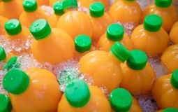 Natural orange juice in orange shape bottles on crushed ice. Ref. Reshing drink with high vitamin C for summer stock image