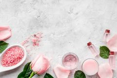 Natural organic cosmetics with rose oil. Cream, lotion, spa salt on grey background top view copyspace. Natural organic cosmetics with rose oil. Cream, lotion stock photo