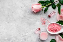Natural organic cosmetics with rose oil. Cream, lotion, spa salt on grey background top view copyspace. Natural organic cosmetics with rose oil. Cream, lotion Royalty Free Stock Image