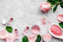 Natural organic cosmetics with rose oil. Cream, lotion, spa salt on grey background top view copyspace. Natural organic cosmetics with rose oil. Cream, lotion stock photos