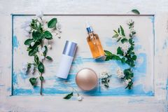 Natural organic cosmetics: serum, cream, mask on wooden background with flowers. Skincare concept stock photos