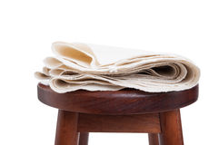 Natural and organic cotton fabric folded sitting on wooden chair Stock Photos