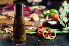 Natural organic oil spices meal seasoning. Natural organic oil and spices in a bottle with vegetables in the background. Meal seasoning and traditional Stock Photos