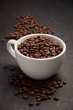 Natural organic roasted coffee beans in white cup on black background Royalty Free Stock Photography