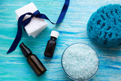 Natural organic soap bottles essential oil and sea salt herbal bath  on a blue wooden table Stock Photos
