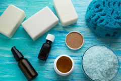 Natural organic soap bottles essential oil and sea salt herbal bath  on a blue wooden table Stock Image