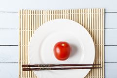 Natural organic tomato and food sticks on white plate. Wooden table with bamboo mat. Chinese and japanese kitchen concept. Top vie. W Royalty Free Stock Image