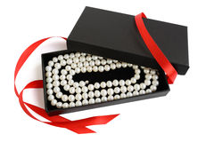 Natural pale pearl necklace in opened black gift box. With red satin ribbon, isolated on white Royalty Free Stock Image