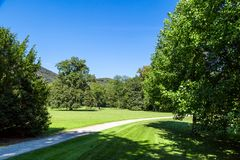 Natural Park in Graz. Landscape view of natural park with path way, meadow area and green big trees among small hills and forest on bright blue sky background Stock Photos