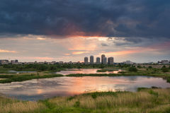Natural park lake in the sunset with some buildings Stock Images