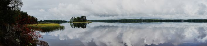 Summer, island on the lake in park Monrepo. In the natural park `Monrepo` in the city of Vyborg there is a lake. There is an island overgrown with trees. The Royalty Free Stock Images