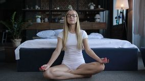 Natural peaceful blonde meditating in bedroom