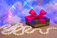 Natural pearl garland and a gift wrapped present with red bow Stock Photography