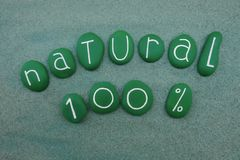 Natural 100 percent composed with green painted stones over green stones. One hundred percent natural, modern slogan for natural products with green painted Stock Photo