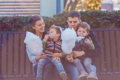 Natural pictures of a happy family of four having fun outsiade and eating sugar floss. A family of four stock images