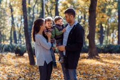 Natural pictures of a happy family of four having fun outsiade on a sunny autumn day. Togetherness and happiness concept royalty free stock photo
